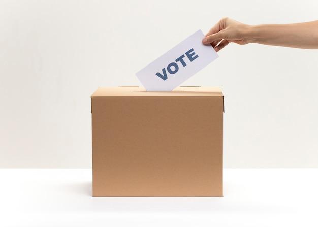 Mão coloca o boletim de voto na caixa de votação Foto Premium