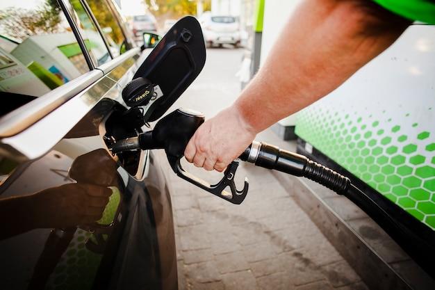 Mão, colocando a bomba de gasolina no tanque do carro Foto gratuita