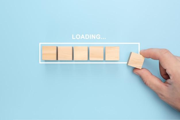 Mão colocando cubo de madeira na barra de carregamento infográfico virtual com formulação de carregamento. Foto Premium