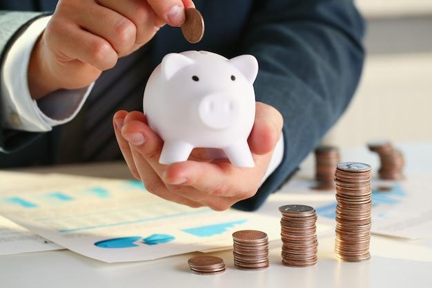Mão colocando dinheiro no porco Foto Premium