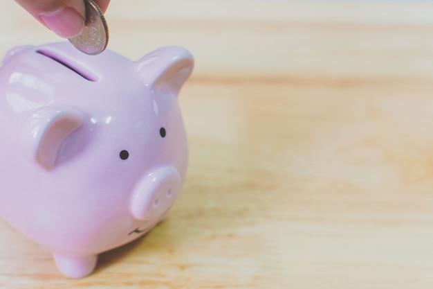 Mão colocando moedas no cofrinho. conceito de poupar dinheiro financiar investimento empresarial Foto Premium