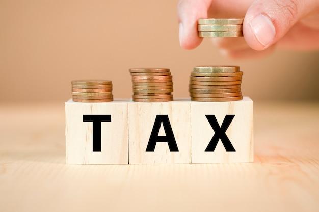 Mão colocando moedas no cubo de madeira e formulação de impostos. conceito de tributação. Foto Premium