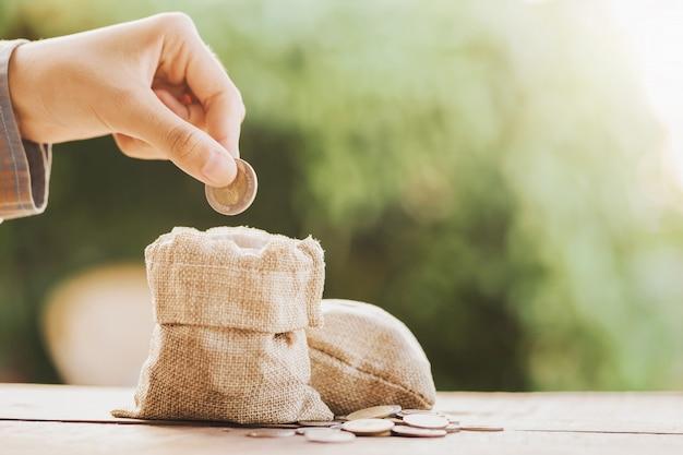 Mão colocando moedas no saco de dinheiro para salvar no fundo da tabela Foto Premium
