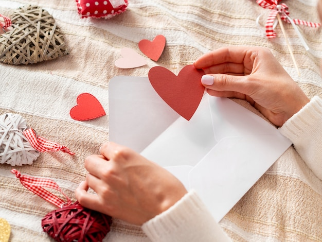 Mão colocando o coração no envelope Foto gratuita