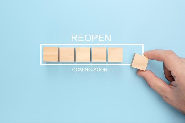 Mão colocando o cubo de madeira na barra de carregamento do infográfico virtual com a redação reopen em breve. Foto Premium