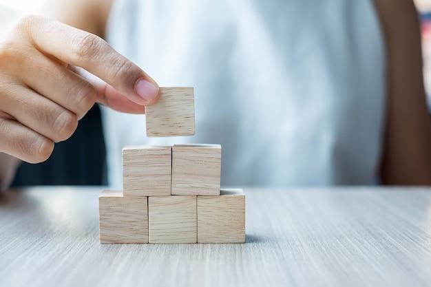 Mão colocando ou puxando o bloco de madeira no edifício. Foto Premium
