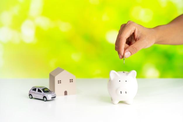Mão coloque moedas no cofrinho com fundo verde da natureza e economizando dinheiro para o conceito de casa e carro Foto Premium