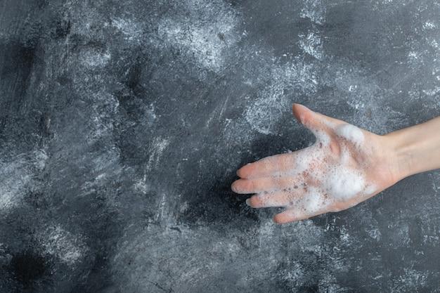 Mão com bolhas de sabão, mostrando a mão no mármore. Foto gratuita