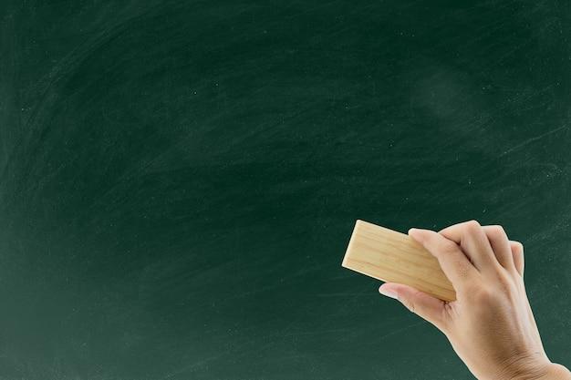 Mão com borracha apaga o quadro-negro, mão com lápis de limpeza de laranja Foto Premium