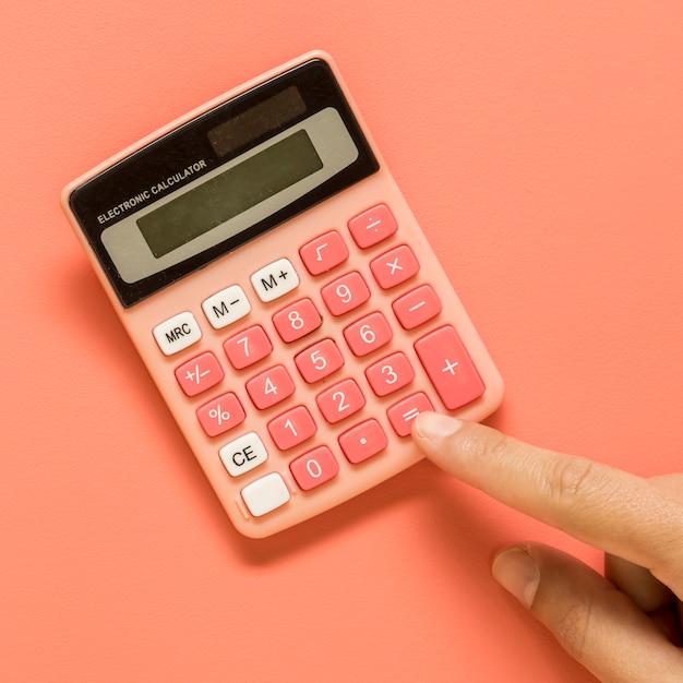 Mão com calculadora rosa na superfície colorida Foto gratuita