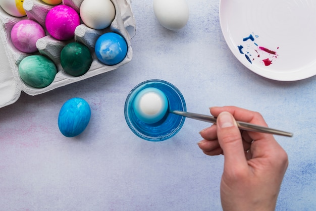 Mão com colher perto de copo de água e ovos de páscoa no recipiente Foto gratuita