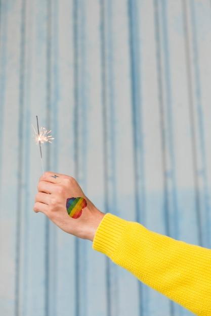 Mão, com, desenhado, arco íris, coração, segurando, queimadura, sparkler Foto gratuita
