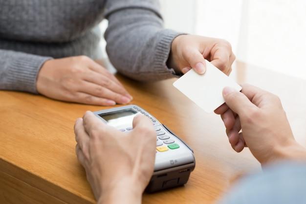 Mão com furto de cartão de crédito através do terminal para pagamento Foto Premium
