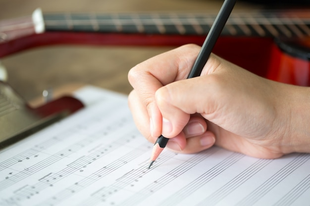 Mão com lápis e folha de música Foto gratuita