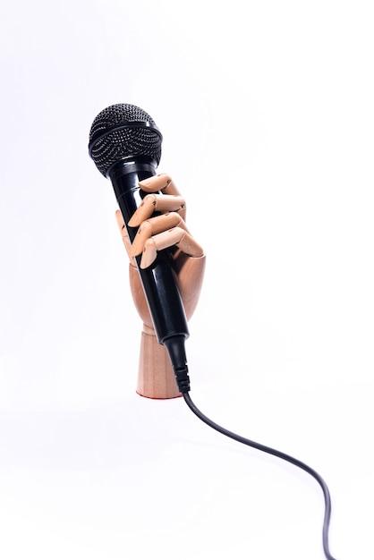 Mão com microfone isolado no fundo branco Foto Premium