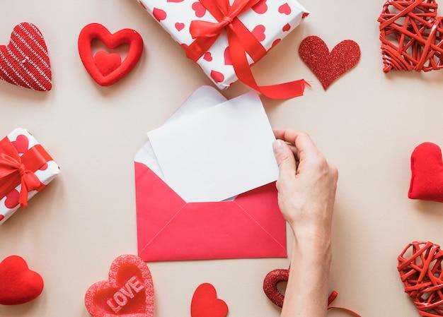 Mão, com, papel, perto, envelope, presentes, e, ornamento, corações Foto gratuita