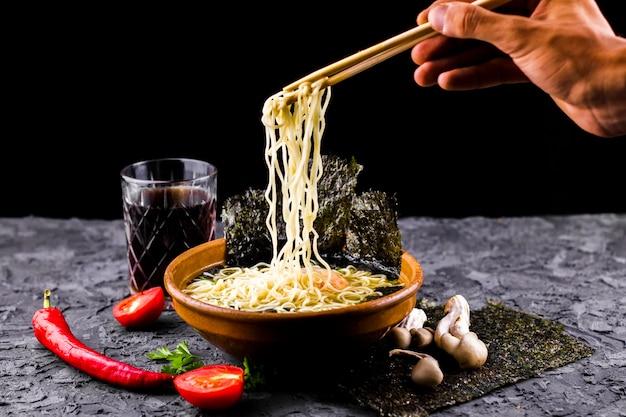 Mão com pauzinhos e sopa de macarrão Foto gratuita