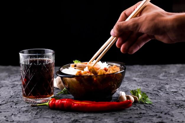 Mão com pauzinhos e tigela de arroz Foto gratuita
