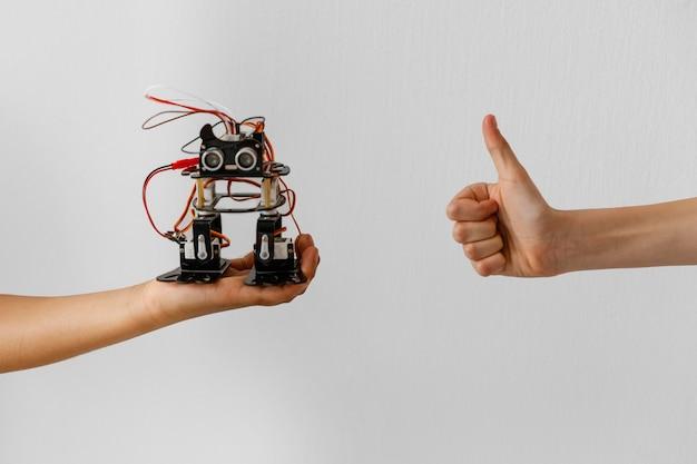 Mão com robô e sinal de ok Foto gratuita