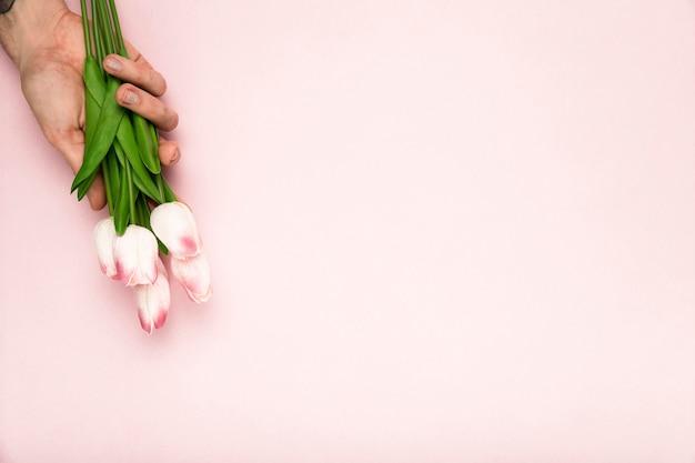 Mão com tulipas e cópia-espaço Foto gratuita