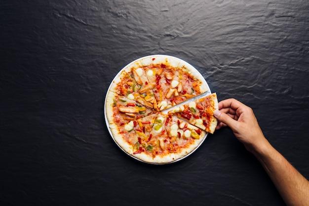 Mão com uma fatia de pizza Foto gratuita