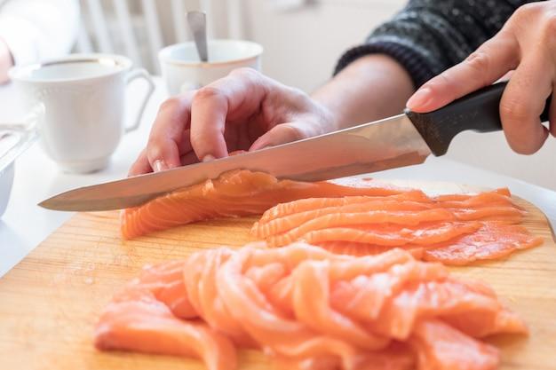 Mão, cozinheiro, usando, faca, fatia, cru, salmão, ligado, tábua cortante Foto Premium