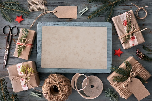 Mão crafted presentes na mesa de madeira rústica com decorações de natal Foto Premium