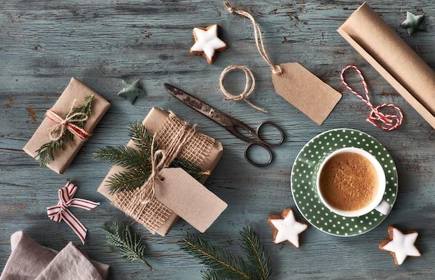 Mão crafted presentes na mesa de madeira rústica escura com decorações de natal Foto Premium