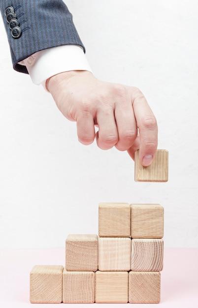 Mão criando escadas de cubos de madeira Foto gratuita