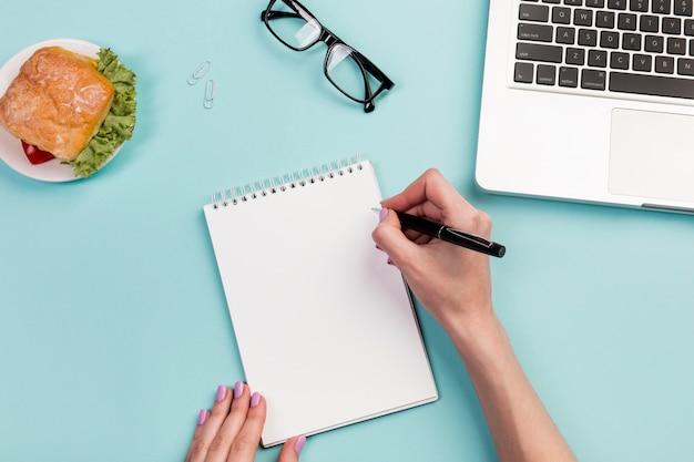 Mão da empresária, escrevendo no bloco de notas em espiral com caneta sobre a mesa do escritório Foto gratuita
