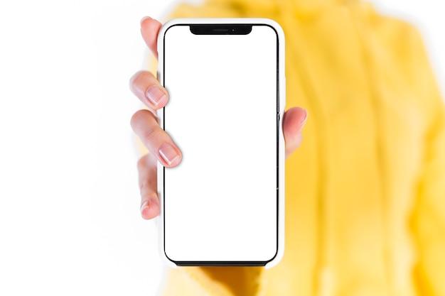 Mão da fêmea, mostrando o celular com tela branca em branco Foto Premium