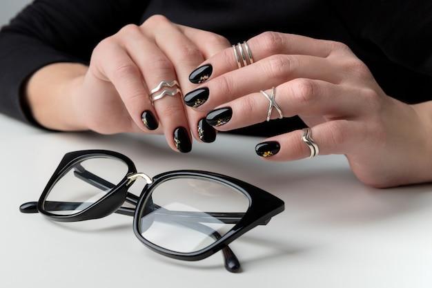 Mão da mulher bonita com manicure elegante. design de unhas preto mínimo. Foto Premium