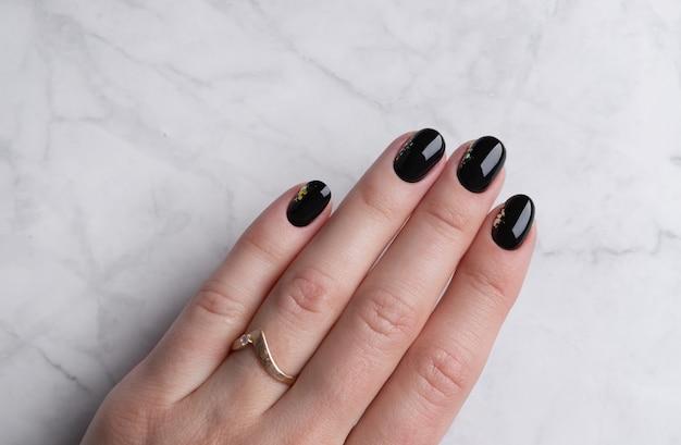 Mão da mulher bonita com manicure elegante em fundo de mármore. design de unhas preto mínimo. Foto Premium