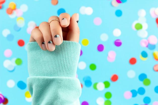 Mão da mulher com confetes coloridos sobre fundo azul. conceito de salão de beleza, moda e spa Foto Premium