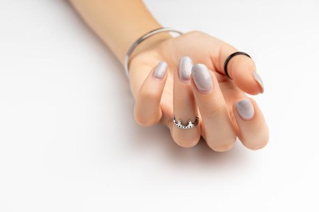 Mão da mulher com manicure crescida em fundo branco com espaço de cópia Foto Premium