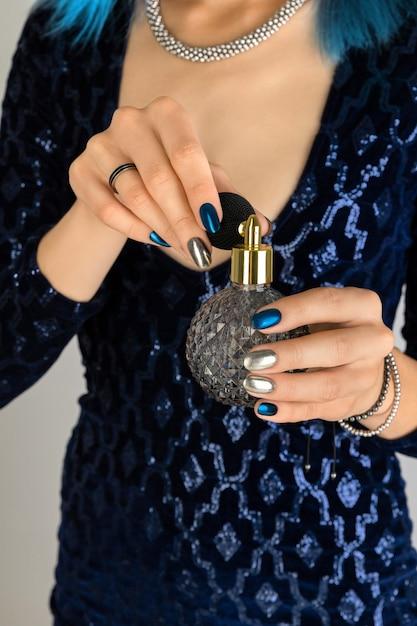 Mão da mulher com manicure segurando o frasco de fundo do perfume. design de unhas de prata noite escura festa. Foto Premium