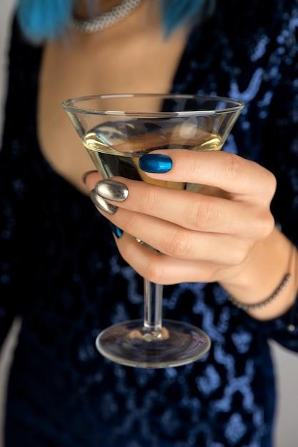 Mão da mulher com manicure segurando um copo de fundo vermute. design de unhas de prata noite escura festa. Foto Premium