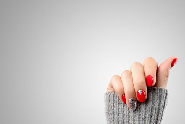 Mão da mulher com manicure vermelha na moda. desenho de unhas de natal de ano novo Foto Premium