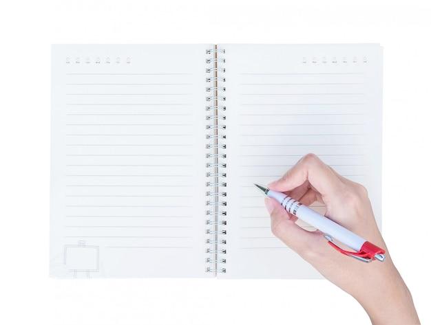 Mão da mulher do close up que escreve no livro de nota com linha na vista superior isolada no fundo branco Foto Premium