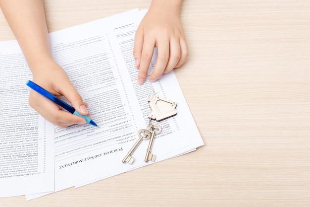 Mão da mulher e tecla home. contrato assinado e chaves da propriedade com documentos Foto Premium