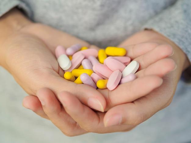 Mão da mulher que guarda muitos comprimidos diferentes. conceito de cuidados de saúde e médico. Foto Premium