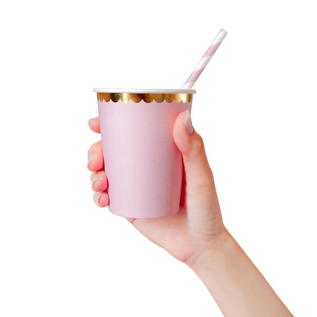 Mão da mulher que guarda o copo de papel cor-de-rosa com as palhas isoladas no fundo branco. Foto Premium
