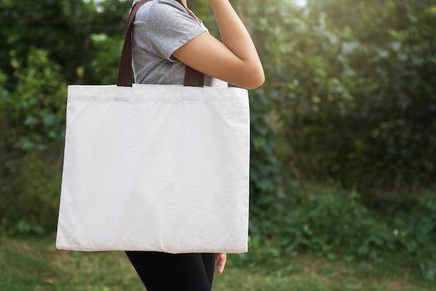 Mão da mulher que guarda o saco do algodão no fundo verde. conceito eco Foto Premium
