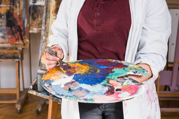 Mão da mulher que mistura a cor da pintura de óleo na paleta na oficina Foto gratuita