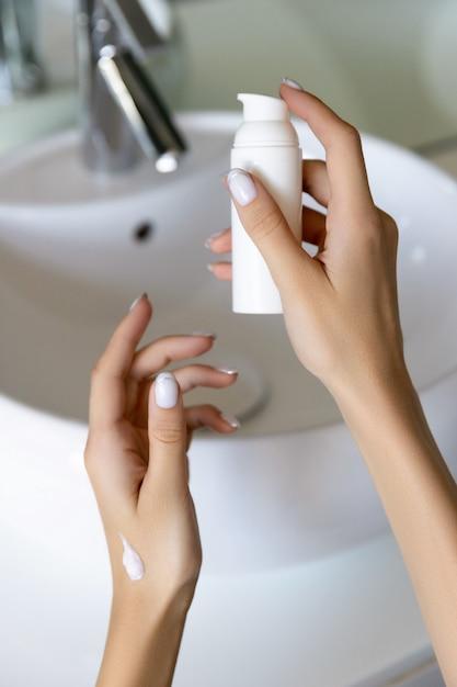 Mão da mulher segurando loção ou creme no banheiro Foto Premium