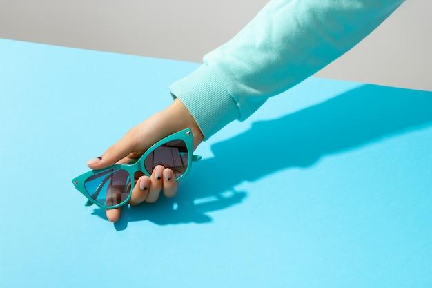 Mão da mulher segurando óculos de sol sobre fundo azul. layout criativo da moda da beleza com o mínimo de elegância Foto Premium