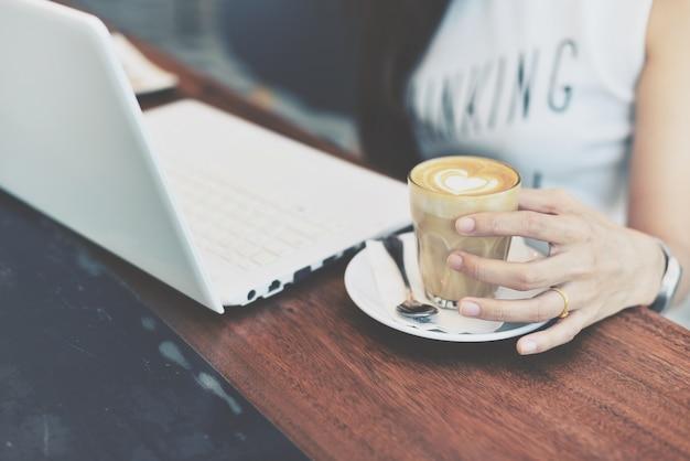 Mão da mulher segurando um copo com copo de café Foto gratuita