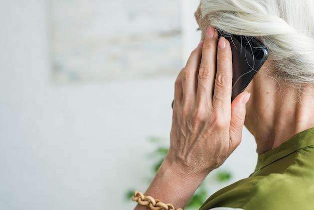 Mão da mulher sênior usando celular Foto gratuita