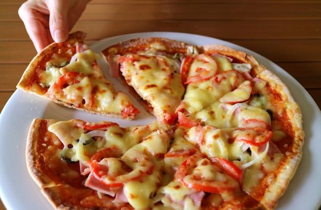 Mão da mulher tomando fatia de presunto e tomate pizza de um prato branco Foto Premium