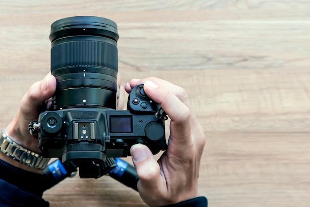 Mão da opinião do close up que guarda a câmara digital com fundo de madeira. Foto Premium
